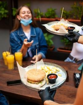 Mulher sorridente recebendo seu pedido de fast food