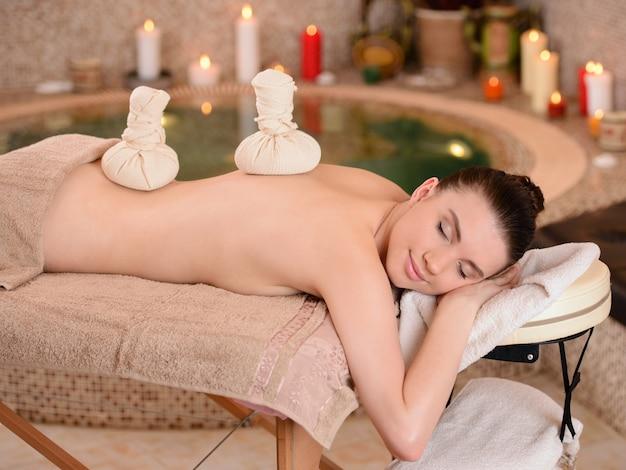 Mulher sorridente recebendo uma massagem nas costas.