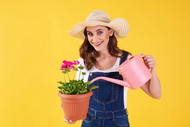 Mulher sorridente regando a flor no estúdio