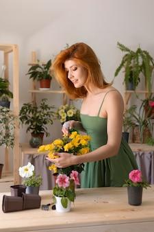 Mulher sorridente regando flor tiro médio