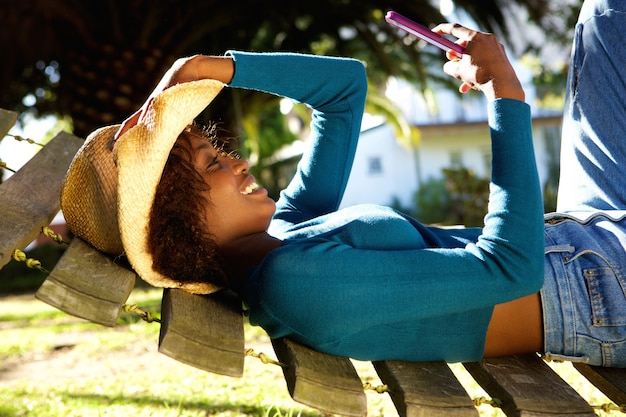 Mulher sorridente, relaxante, ligado, rede, com, telefone móvel