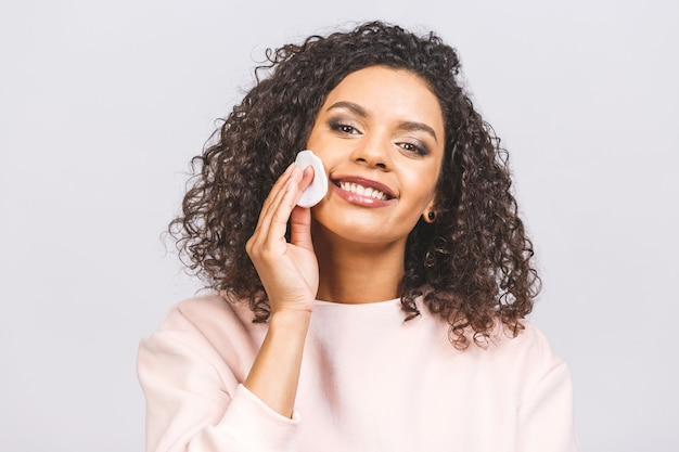 Mulher sorridente, removendo a maquiagem. foto de uma mulher afro-americana mantém almofadas de algodão perto do rosto isolado no fundo branco. conceito de cuidados com a pele e beleza.
