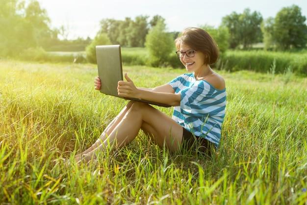 Mulher sorridente repousa na natureza e fala em vídeo chamada