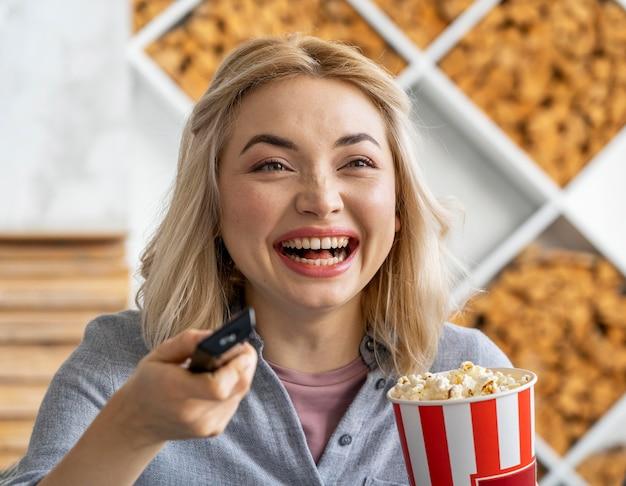 Mulher sorridente rindo enquanto assiste a um filme
