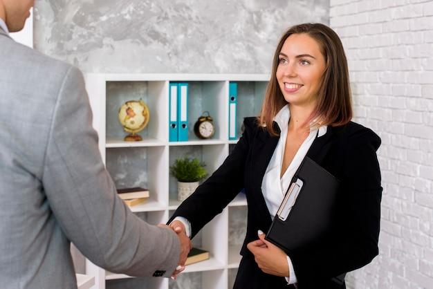 Mulher sorridente sacode a mão do cliente