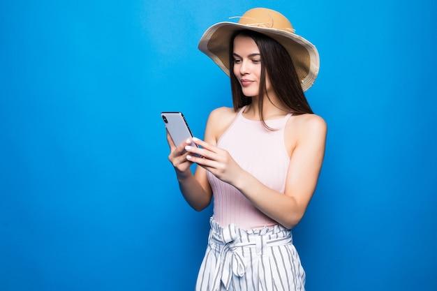 Mulher sorridente satisfeita digitando mensagem de texto ou percorrendo redes sociais usando smartphone isolado sobre a parede azul.