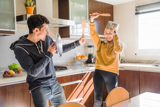 Mulher sorridente se divertindo com o marido na cozinha