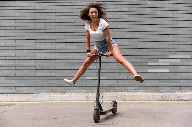 Mulher sorridente se divertindo com scooter ao ar livre