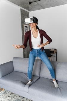Mulher sorridente se divertindo em casa com fone de ouvido de realidade virtual