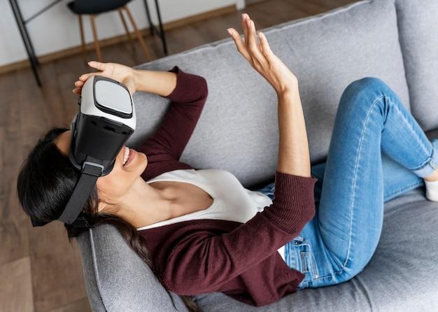 Mulher sorridente se divertindo em casa no sofá com fone de ouvido de realidade virtual