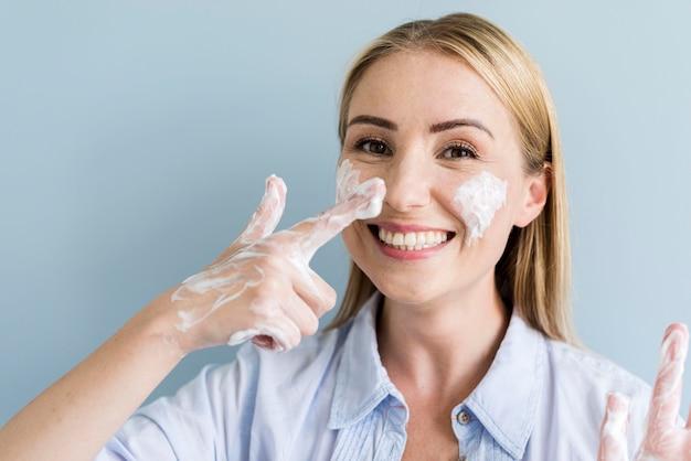 Mulher sorridente se divertindo enquanto lava as mãos e o rosto