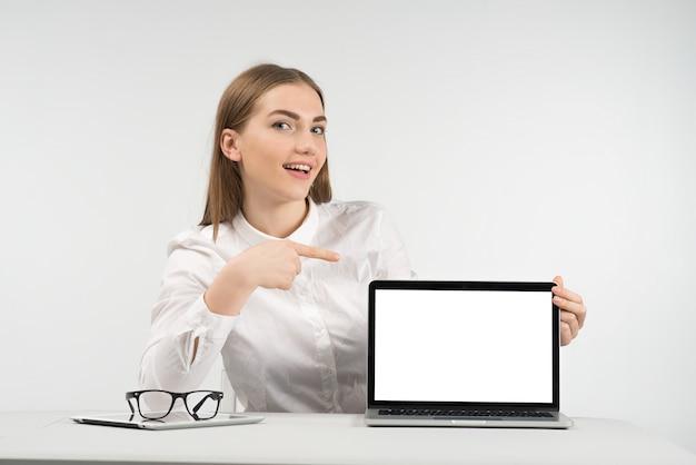 Mulher sorridente se senta à mesa e aponte para a tela, olhando para a câmera