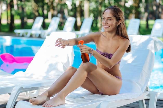 Mulher sorridente se sentindo alegre enquanto toma banho de sol perto da piscina e usa proteção solar