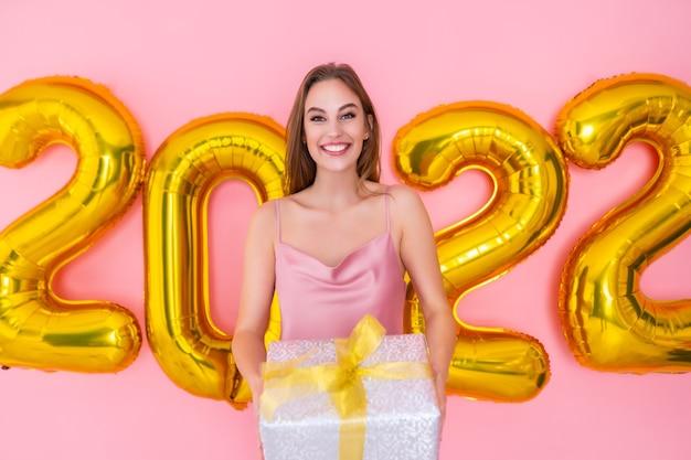 Mulher sorridente segura caixa de presente isolada na celebração de ano novo de balões de ar de fundo rosa