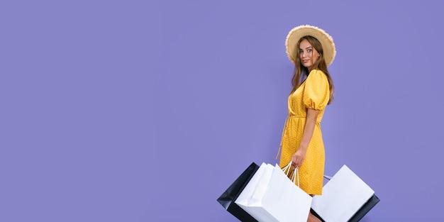 Mulher sorridente segura pacotes depois de fazer compras em fundo roxo com descontos em vendas de sexta-feira negra