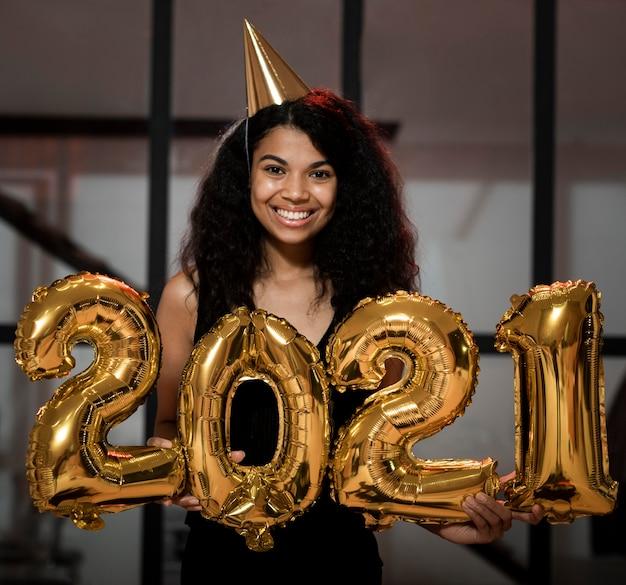 Mulher sorridente segurando 2.021 balões na festa