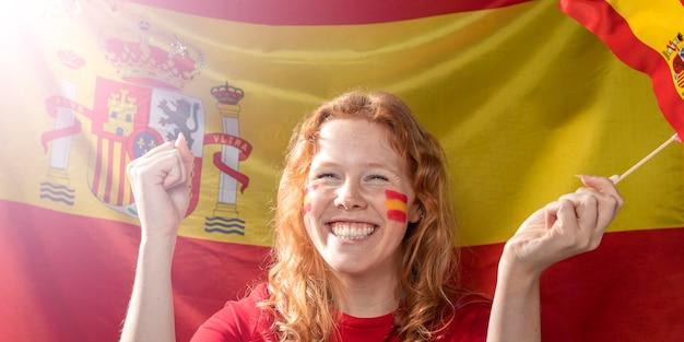 Mulher sorridente segurando a bandeira da espanha