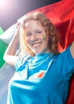 Mulher sorridente segurando a bandeira italiana
