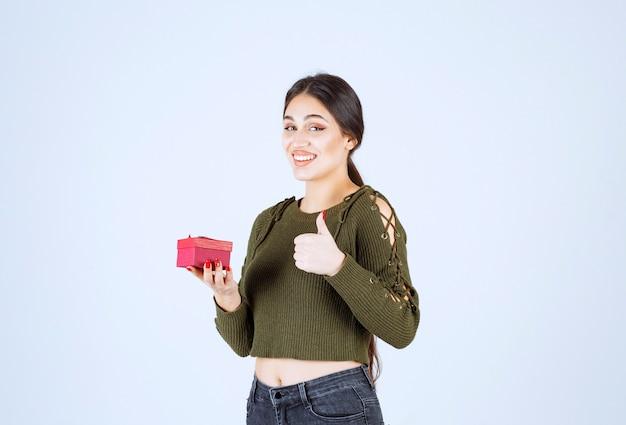 Mulher sorridente segurando a caixa de presente e dando polegares para cima em fundo branco.