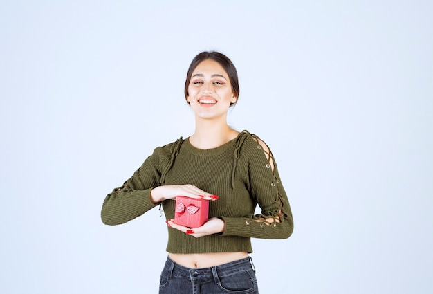 Mulher sorridente segurando a caixa de presente e olhando para a câmera no fundo branco.