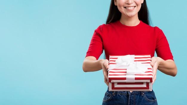 Mulher sorridente segurando a caixa de presente