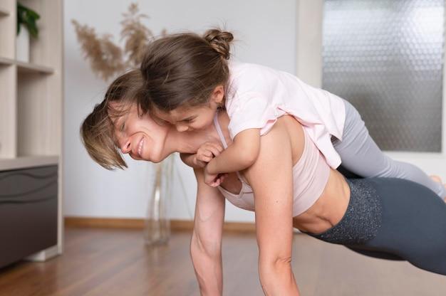 Mulher sorridente segurando a garota nas costas