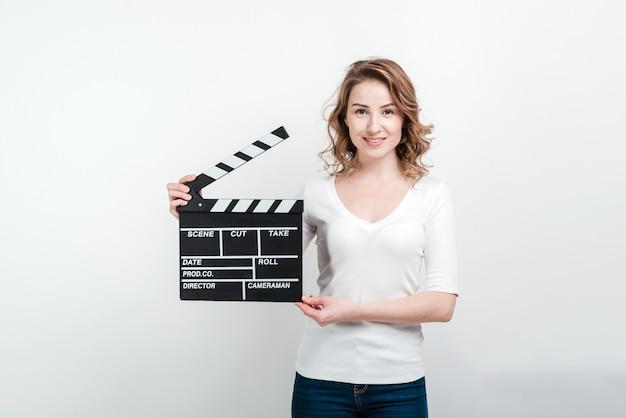 Mulher sorridente segurando a placa de filme.