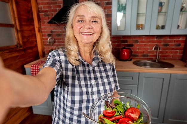 Mulher sorridente segurando a tigela com salada
