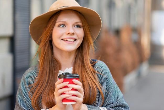 Mulher sorridente segurando a xícara de café