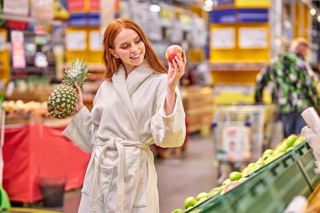 Mulher sorridente segurando abacaxi e maçã nas mãos na loja, senhora caucasiana em roupão de banho em compras