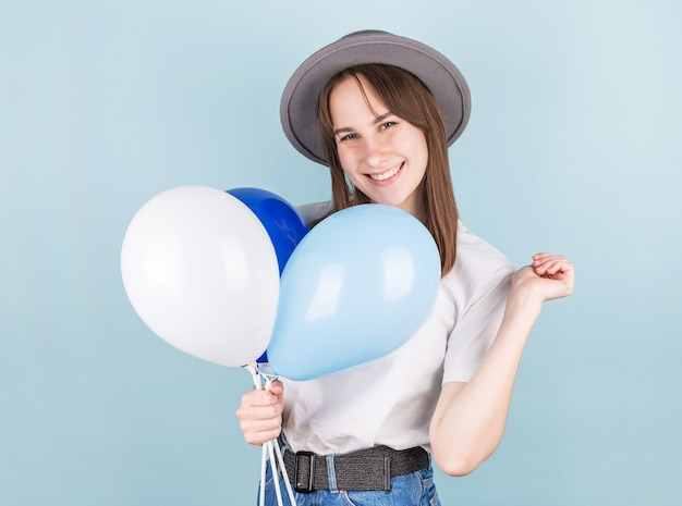 Mulher sorridente segurando balão e olhando para a câmera sobre fundo azul.