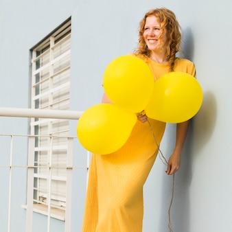 Mulher sorridente segurando balões amarelos
