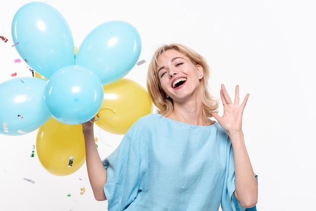 Mulher sorridente, segurando balões