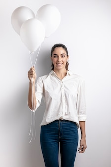 Mulher sorridente segurando balões