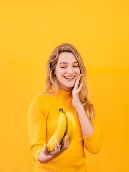Mulher sorridente segurando bananas