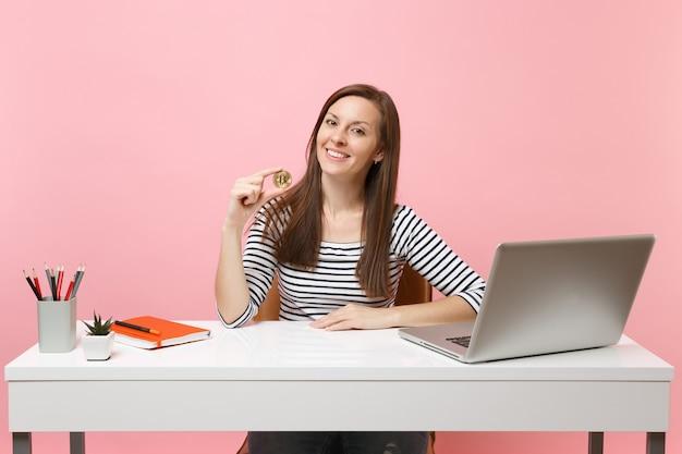 Mulher sorridente segurando bitcoin, moeda de metal dourada, futura moeda sentada no trabalho na mesa branca com o laptop do pc