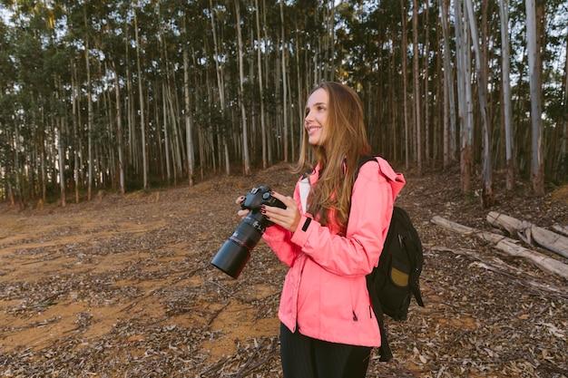 Mulher sorridente, segurando, câmera, em, floresta