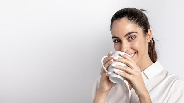 Mulher sorridente segurando caneca com espaço de cópia