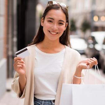 Mulher sorridente segurando cartão de crédito e sacolas de compras ao ar livre