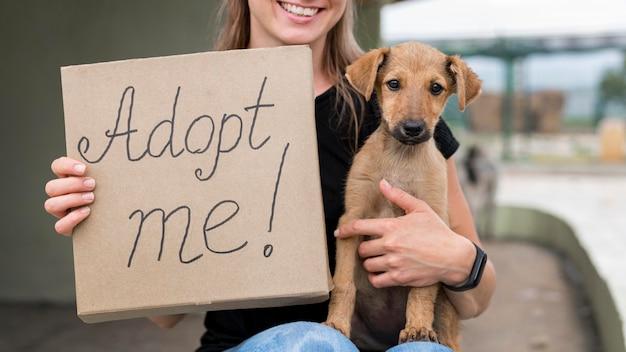 Mulher sorridente segurando cartaz de me adote e resgate cachorro
