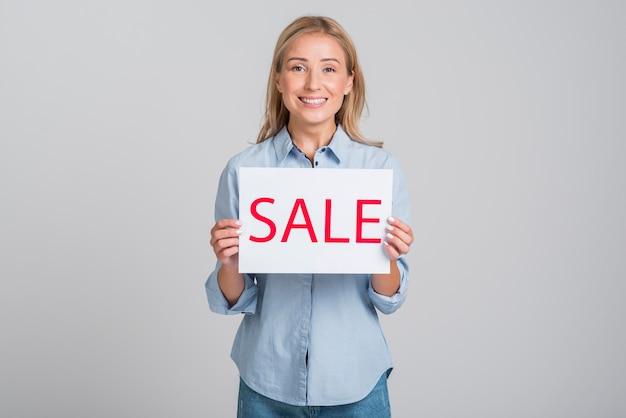 Mulher sorridente segurando cartaz de venda