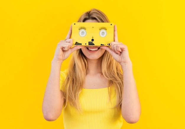Mulher sorridente segurando cassete