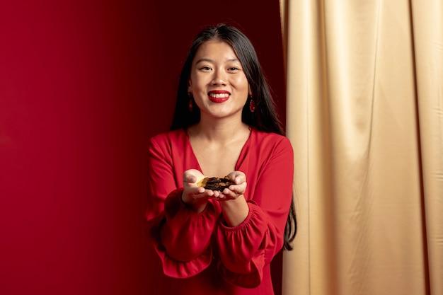 Mulher sorridente segurando confete dourado nas mãos