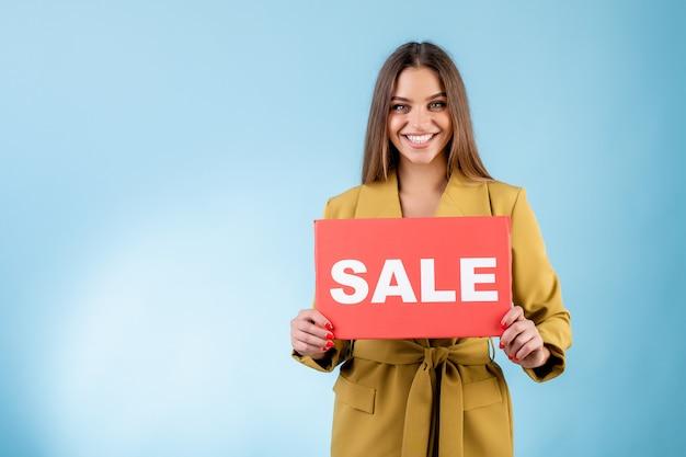 Mulher sorridente segurando cópia espaço vermelho sinal de venda isolado sobre azul