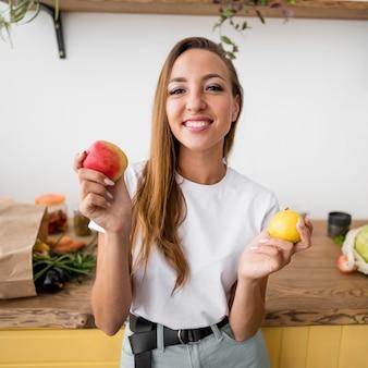 Mulher sorridente segurando duas frutas