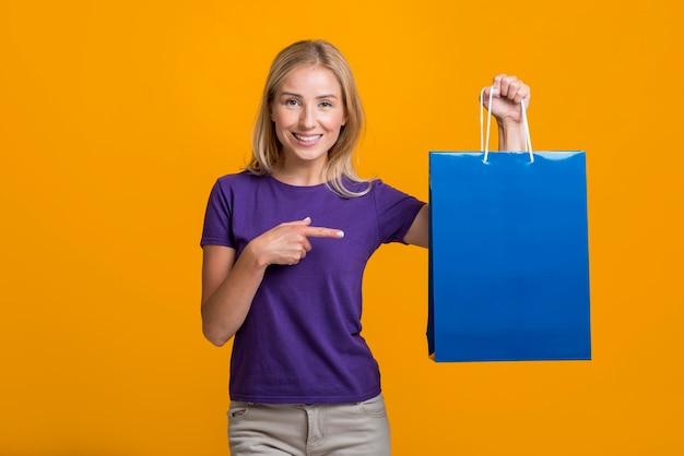 Mulher sorridente segurando e apontando para a sacola de compras