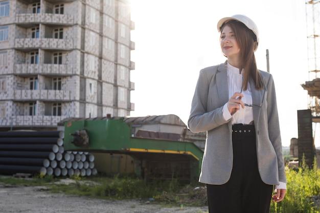 Mulher sorridente, segurando, espetáculo, ficar, em, local construção, olhando