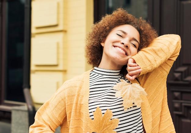 Mulher sorridente segurando folhas ao ar livre