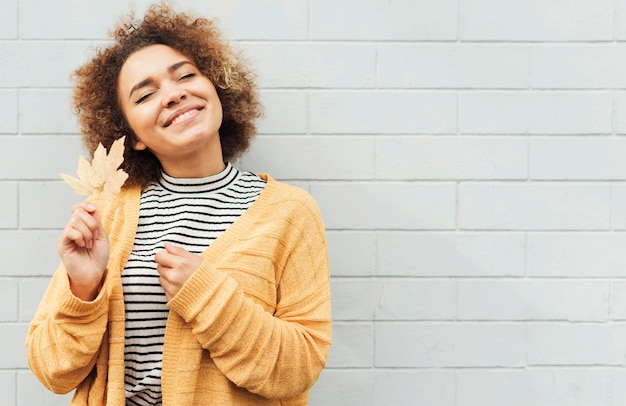 Mulher sorridente segurando folhas outonais do lado de fora