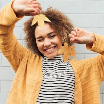 Mulher sorridente segurando folhas outonais